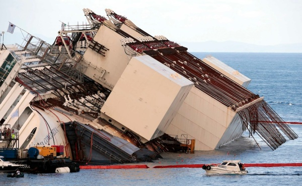 "Salvage crew workers are seen in front of  the capsized cruise liner Costa Concordia after the start of the ""parbuckling"" operation outside Giglio harbour"